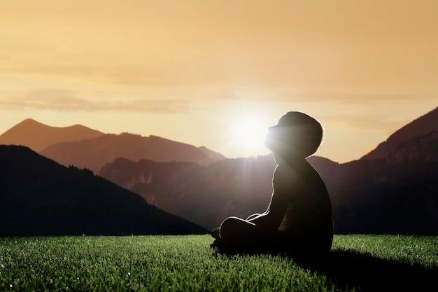 Dziecko siedzi na szczycie góry o zachodzie słońca i marzy