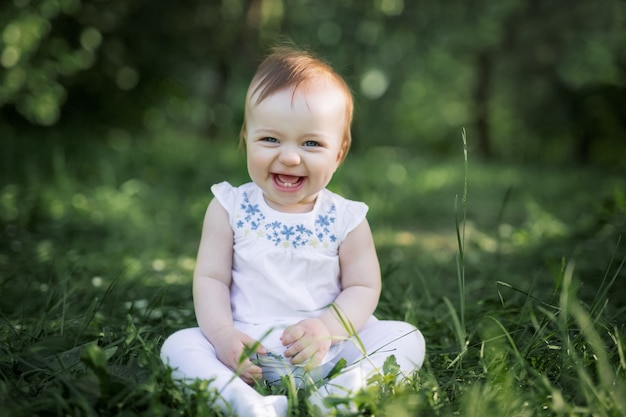 Dziecko siedzi na zielonej trawie w parku i się śmieje. pierwsze dwa zęby dziecka