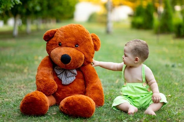 Dziecko siedzi na zielonym trawniku w lecie z dużym misiem