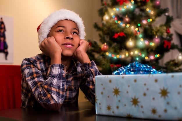 Dziecko siedzi obok prezentu świątecznego.