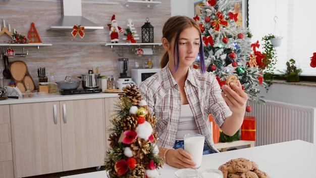 Dziecko siedzi przy stole w udekorowanej kuchni je tradycyjne świąteczne ciasteczka pijące mleko