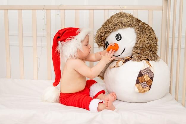 Dziecko siedzi w czapce mikołaja z bałwanem w żłobku w łóżeczku