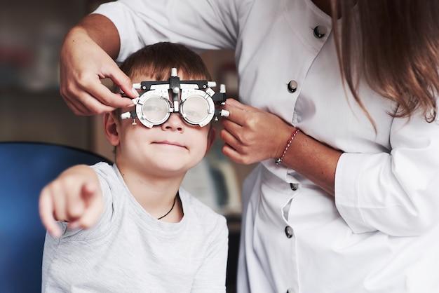 Dziecko siedzi w gabinecie lekarskim i przetestowało jego ostrość wzroku.
