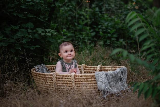 Dziecko siedzi w kołysce z wikliny słomy w zielonym parku. mała dziewczynka w ładny strój, uśmiechając się. portret.
