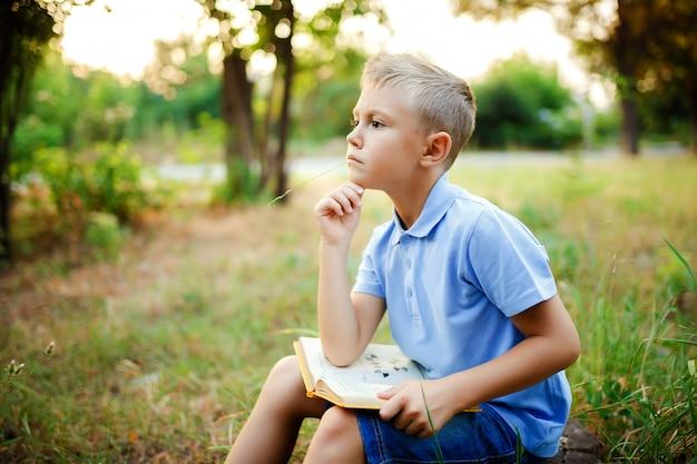 Dziecko siedzi w lesie z książką na kolanach i odwraca wzrok.