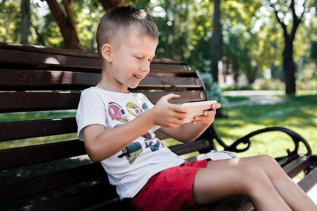 Dziecko siedzi w parku na ławce z gadżetem. dzieci korzystają z gadżetów. chłopiec gra w grę na telefonie komórkowym.