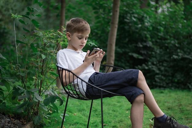 Dziecko siedzi w przyrodzie i patrzy na telefon. gadżety współczesnej generacji