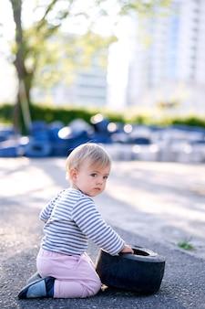 Dziecko siedzi z odwróconą głową i dotyka obręczy auta na parkingu