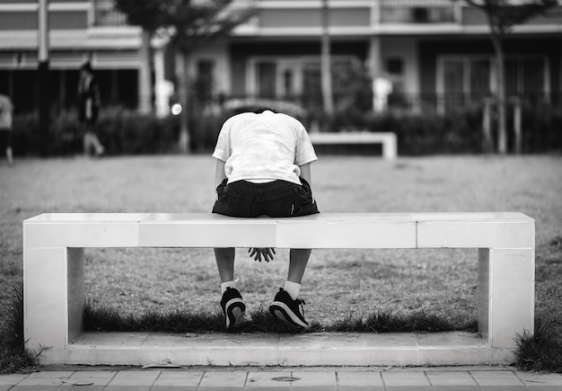 Dziecko siedziało na smutnym, kwadratowym krześle w parku
