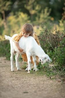 Dziecko śliczna dziewczyna w żółtej bawełnianej sukience bawi się i przytula białą kozę na wsi, lato natura na zewnątrz. przyjaźń dziecka i zwierząt gospodarskich. pionowy