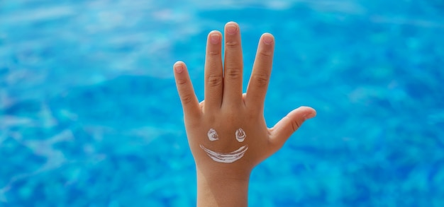 Dziecko smaruje jej dłoń kremem przeciwsłonecznym. selektywne skupienie. dziecko.