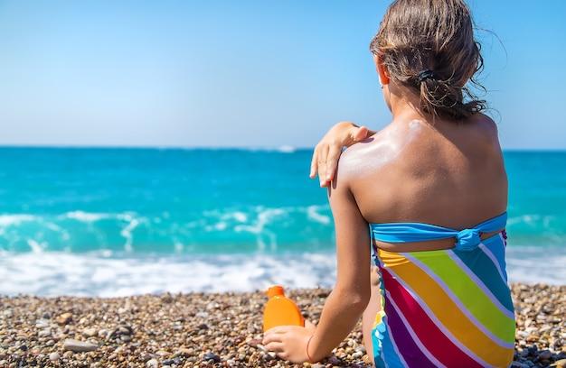 Dziecko smaruje jej plecy kremem przeciwsłonecznym. selektywne skupienie. dziecko.