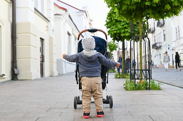 Dziecko spaceruje po mieście z wózkiem. widok z tyłu
