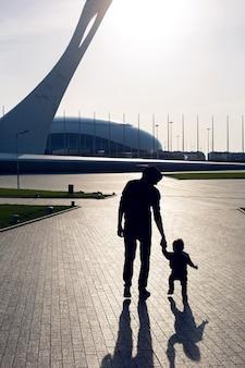 Dziecko spaceruje z ojcem sylwetkami po parku na placu w soczi