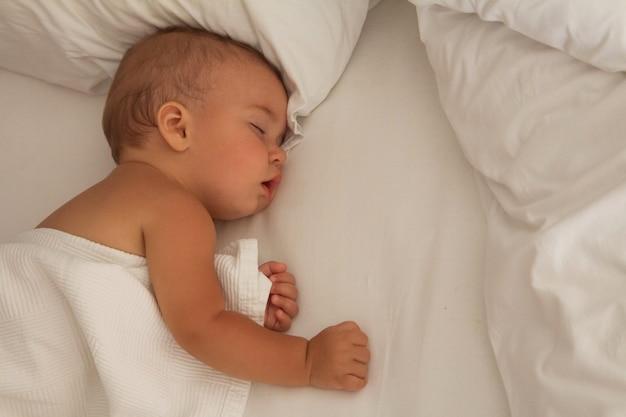 Dziecko śpi na białej poduszce z białym kocem