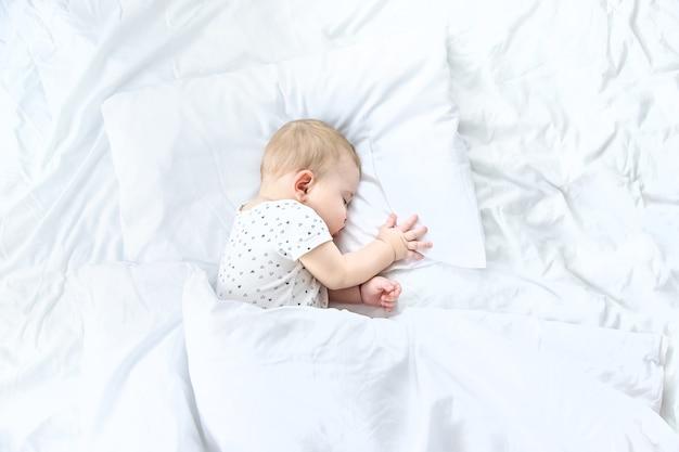 Dziecko śpi na białym łóżku