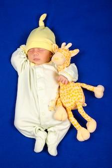 Dziecko śpi na niebieskim kocu. mały chłopiec w piżamie drzemał