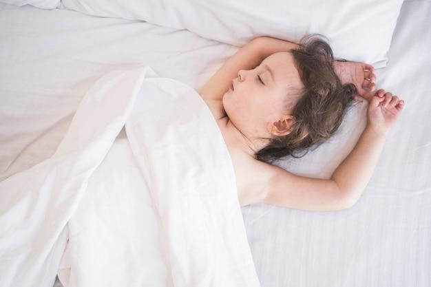 Dziecko śpi słodko w łóżku śpiące dzieci w łóżku rodziców dziecko śpi spokojnie na ...