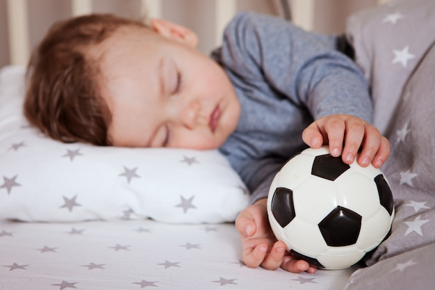 Dziecko śpi w łóżeczku z piłką nożną w ręku.