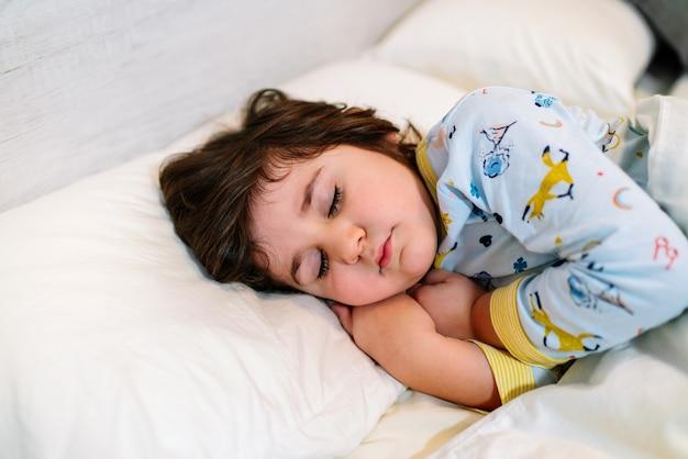 Dziecko śpiące w łóżku z zamkniętymi oczami i niewinną twarzą, ubrane w piżamę i białą pościel