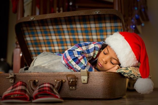 Dziecko śpiące w przytulnej walizce. świąteczna drzemka chłopca w walizce. mały mikołaj potrzebuje odpoczynku. przytulne miejsce do spania.