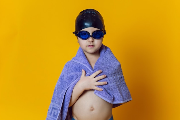 Dziecko-sportowiec w niebieskich okularach do pływania i czarnej gumowej czapce i ręczniku stoi na żółtej ścianie