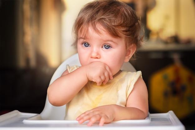 Dziecko ssie ręce, pierwsze zęby. dziecko siedzi w foteliku i wygląda przez okno