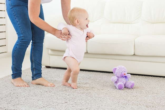 Dziecko stawia pierwsze kroki z pomocą mamy w domu