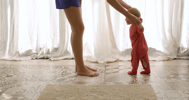 Dziecko stawia pierwsze kroki z pomocą matki