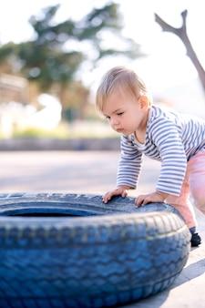 Dziecko stoi i opiera się o oponę samochodu na parkingu