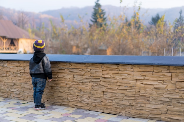 Dziecko stoi przy ogrodzeniu i odwraca wzrok