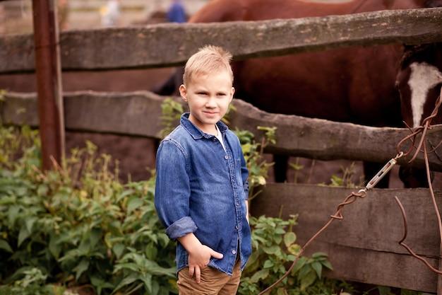 Dziecko stoi w pobliżu drewnianego płotu z końmi