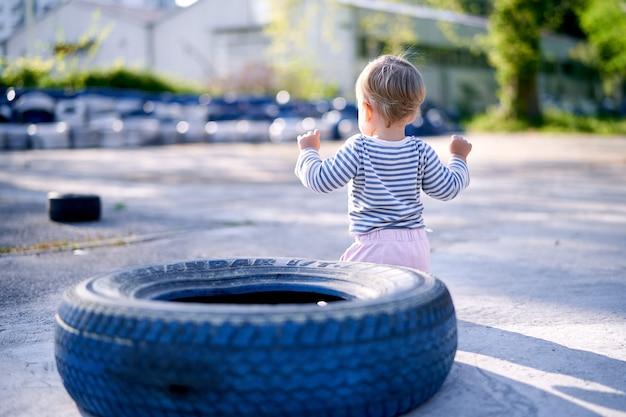 Dziecko stoi w pobliżu opony samochodowej na parkingu, widok z tyłu