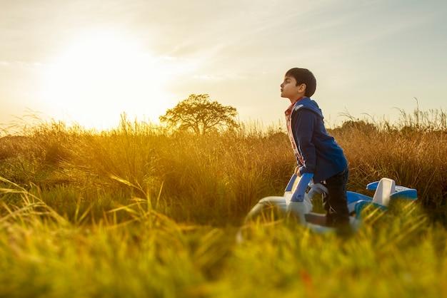 Dziecko stojące na środku wsi, w swoim samochodziku patrzy na ścieżkę