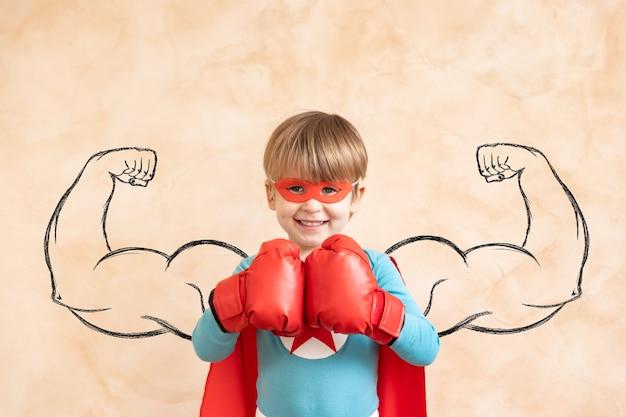 Dziecko superbohatera bawiące się w domu.