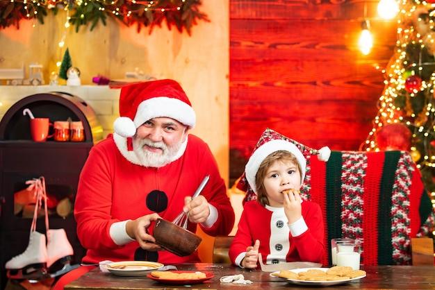 Dziecko święty mikołaj cieszy się w serwowane ciasto piernikowe i mleko
