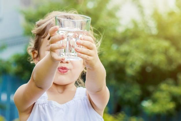 Dziecko szklankę wody. selektywna ostrość.