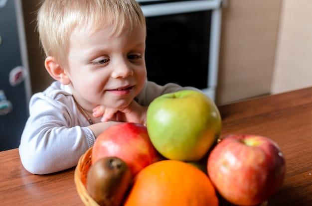Dziecko szuka owoców i uśmiecha się.