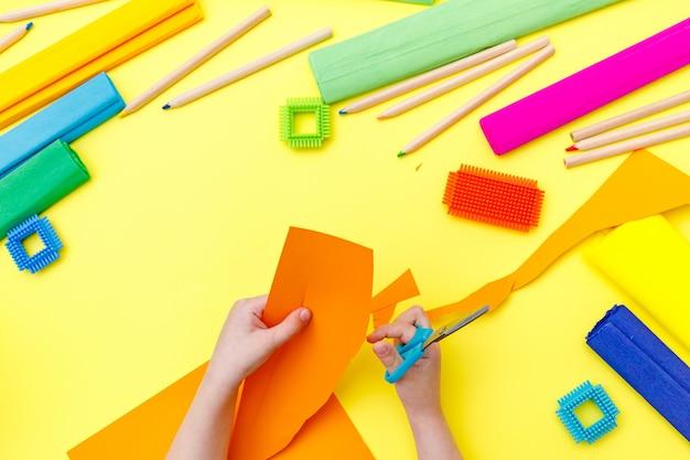 Dziecko tnące kolorowy pomarańczowy papier z nożyczkami na stole do jakiegoś rękodzieła