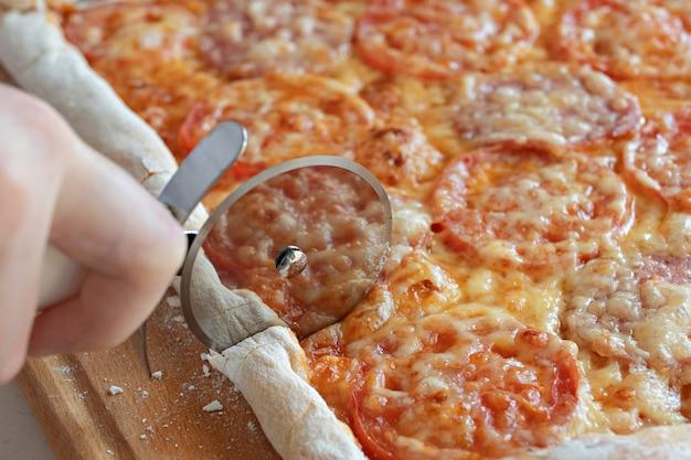 Dziecko tnie pizzę z rolką krajarki z bliska
