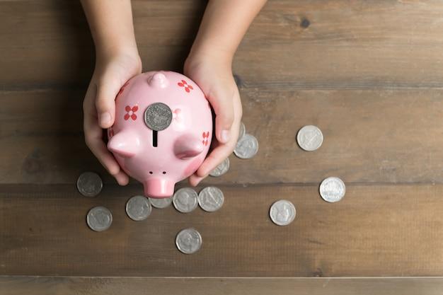 Dziecko trzyma bank świni na tle starego drewna, oszczędzając pieniądze na przyszłość koncepcji edukacji i