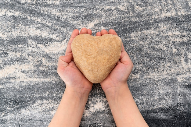 Dziecko trzyma ciasto w kształcie serca. domowe ciasteczka z miłością.