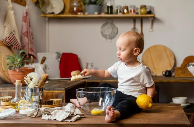 Dziecko trzyma cytrynę i szczotka pełny strzał