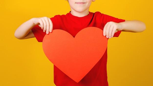 Dziecko trzyma czerwone serce. koncepcja miłości, dobroczynności i darowizny społecznej. słodkie dziecko z czerwonym papierowym sercem.