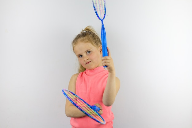 Dziecko trzyma dwie niebieskie rakiety tenisowe. poza sportowa. zabawa