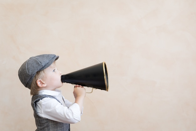 Dziecko trzyma głośnik. dziecko krzyczy przez megafon vintage. koncepcja wiadomości biznesowych