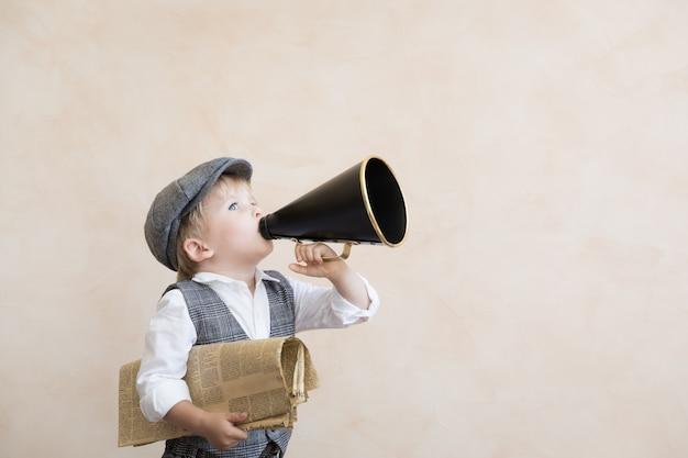 Dziecko trzyma głośnik i gazetę. dziecko krzyczy przez megafon vintage. koncepcja wiadomości biznesowych