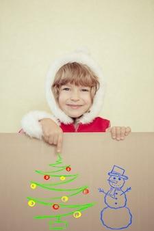 Dziecko trzyma kartkę świąteczną z narysowanego drzewa i bałwana. koncepcja świątecznych wakacji