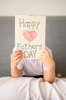 Dziecko trzyma kartkę z życzeniami dzień ojca