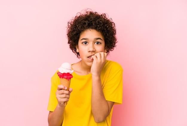 Dziecko trzyma lody i gryzie paznokcie